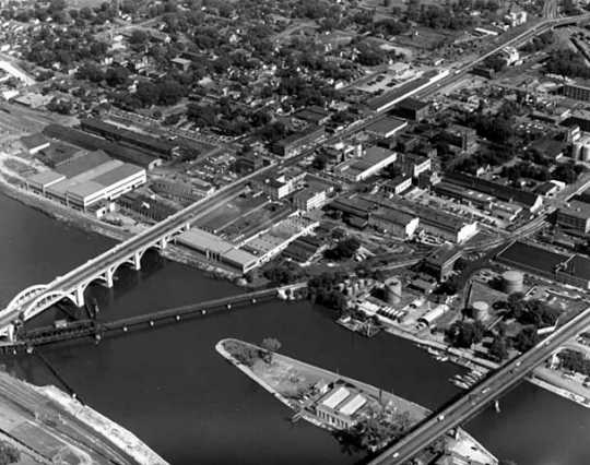 Black and white aerial view of the Flats, 1953, showing Robert, Wabasha, and railroad bridges and American Hoist and Derrick facilities.