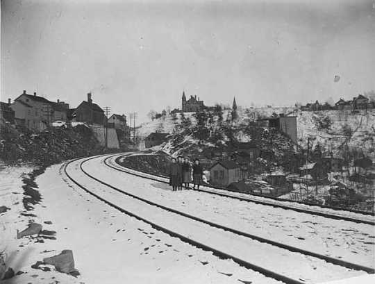 Black and white photograph of the Swede Hollow neighborhood taken from the St. Paul and Duluth Railroad tracks, c.1910.