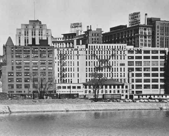 Black and white photograph of the West Publishing complex seen from the Mississippi River, 1955.
