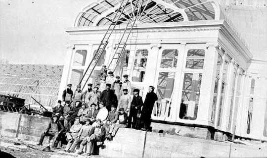 Black and white photograph of construction workers in front of the conservatory, ca. 1915.