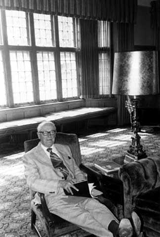 Black and white photograph of Sy Mergens relaxing in the Fireside Room of the University Club, June 22, 1977. Photographed by Julian G. Plante.