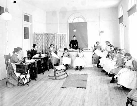 Black and white photograph of sewing class at the State School, c.1905.
