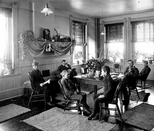 Black and white photograph of the interior of Cottage One at the State School, c.1900.
