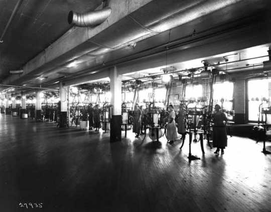 Photograph of a row of women at knitting machines at the Munsingwear factory