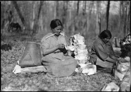 Photograph of Mary Bigwind and Maggie Skinaway making birch bark containers for maple sap