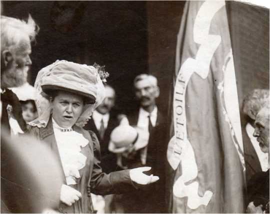 Black and white photograph of Mary Mehegan Hill speaking at a St. Paul event marking the fiftieth anniversary of the First Minnesota Volunteer Infantry Regiment's departure for Civil War duty, 1911.. Hill presented a duplicate of an old Regimental flag to the group.