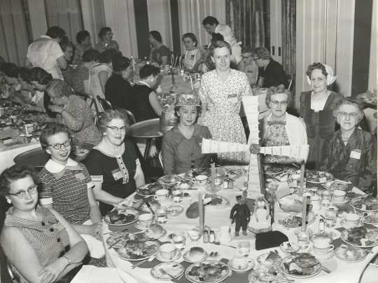 Black and white photograph of Crookston BPW club members at a table representing Denmark during an international breakfast event, 1958.