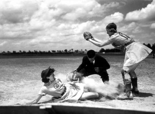 All American Girls Professional Baseball League player Marg Callaghan sliding into home plate as umpire Norris Ward watches (Opalocka, Florida)