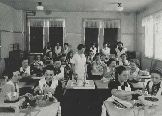 Black and white photograph of Retta Bede with students during a home-cooking class, 1930s.