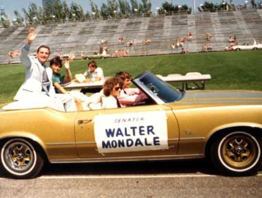 Senator Walter Mondale waves from the back of a car in the Minneapolis Aquatennial Parade, 1972