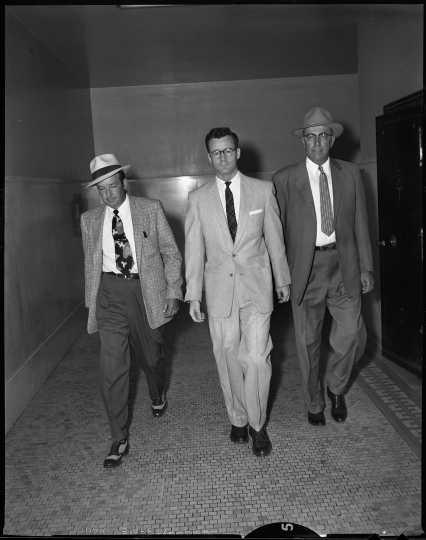 James P. Taylor (center) in police custody on July 5, 1956, the day he was sentenced to life in prison without parole for the murder of Kenneth Lindberg. Box 423 of the Minneapolis Star Tribune negatives collection, Minnesota Historical Society, St. Paul.