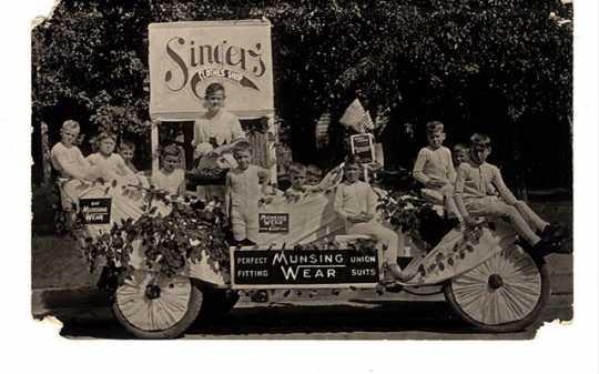 photograph of children on a parade float wearing Munsingwear long underwear.