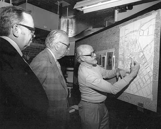 Paul Granlund looking at a map of St. Paul with Russell Fridley and Elmer L. Andersen