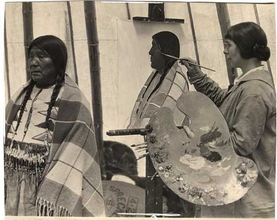Black and white photograph of Elsa Jemne painting portrait of a Blackfoot woman, c.1915