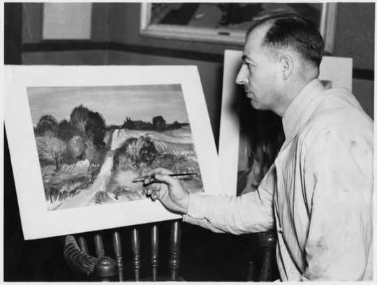 Black and white photograph of Cameron Booth posing with a watercolor, 1937.