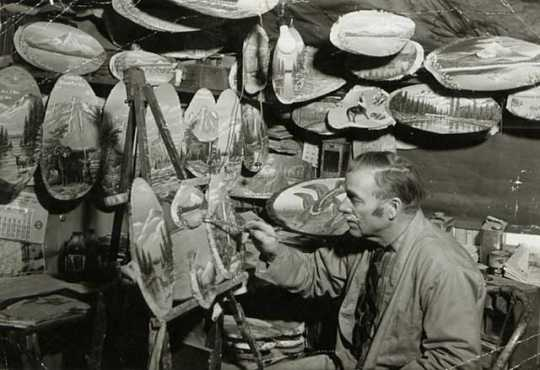 Photograph of Andrew Stenstrom, a lumberjack sky pilot and primitive painter, painting souvenir items in his Bemidji studio c.1940.