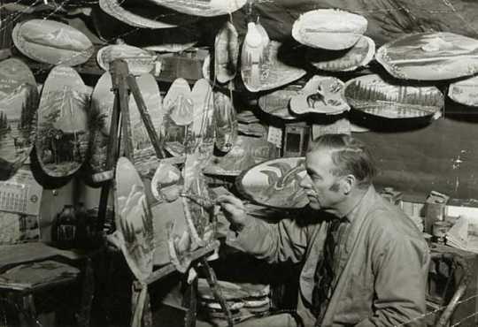 Photograph of Andrew Stenstrom, a lumberjack sky pilot and primitive painter, painting souvenir items in his Bemidji studio c.1940.