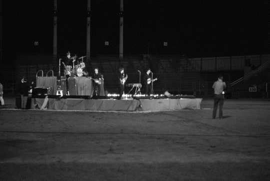 Black and white photograph of The Beatles in concert at Metropolitan Stadium, Bloomington, August 21, 1965. Photograph: Neale, St. Paul Dispatch & Pioneer Press.