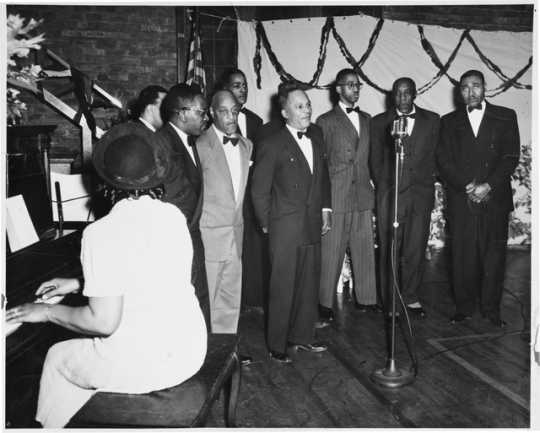 The Wheatley Aires, a men's singing group, sing in front of an audience at Phyllis Wheatley Community Center (809 Aldrich Avenue North) with a pianist accompanying. ca. 1950.