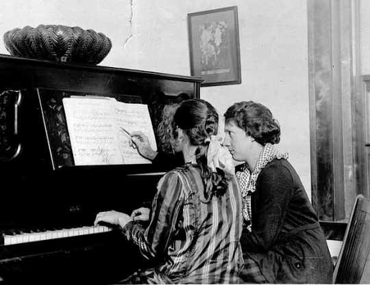 Black and white photograph of a girl being given piano lesson at the Northeast Neighborhood House, c.1925.
