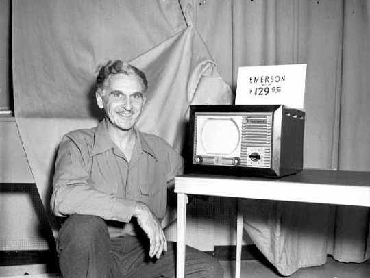 Black and white photograph of a WTCN-TV employee with an Emerson television set, 1949.