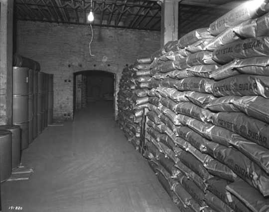 Black and white photograph of sacks of sugar produced by the American Crystal Sugar Company sit in a storage warehouse. Photographed by Norton & Peel on November 30, 1949