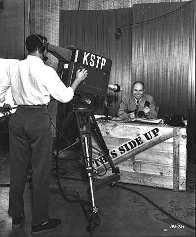 Black and white photograph of a KSTP-TV cameraman filming the This Side Up program, 1950.