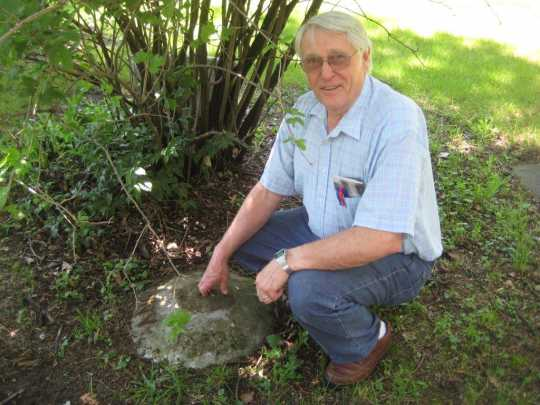 Color image of Norman Ewert, ca. 2013, with a disk blade he made as a temporary tombstone for the grave of Anna Funk Wiens inside Carson Mennonite Brethren Church Cemetery.