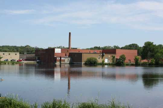 Color image of north and west façades of Faribault Woolen Mill with Cannon River in the foreground, 2011.