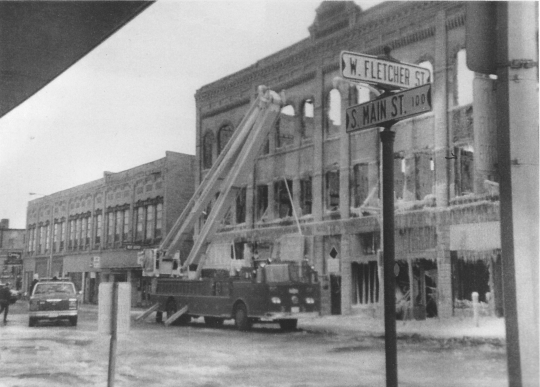 Black and white photograph of a fire truck outside the Opera House Block on South Main Street after the 1987 fire.