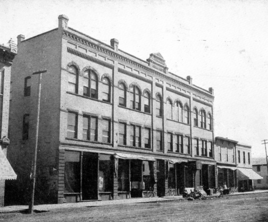 Black and white photograph of the façade of the Opera House Block on South Main Street as it looked in 1910.