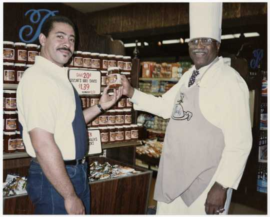 Oscar C. Howard (right) and a Byerly's grocery store employee near a display of Chef Oscar's BBQ Sauce, ca. 1980s. Oscar C. Howard papers, 1945–1990 (P1842), Cafeteria and Industrial Catering Business, 68601, Manuscripts Collection, Minnesota Historical Society, St. Paul.