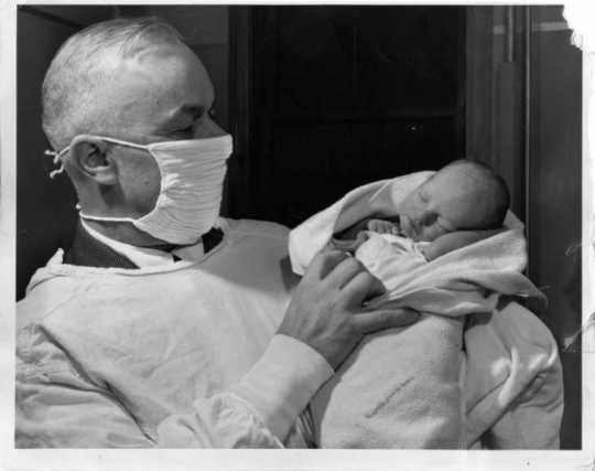 Dr. Russell Heim with a baby left at his office (12 West Lake St., Minneapolis), 1947. Photograph by Paul Siegel. Published in the Minneapolis Morning Tribune, October 31, 1941.