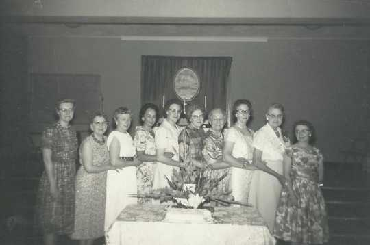 Black and white photograph of ten past BPWC presidents pose for a group photograph, 1961. From left to right: Gudvieg Norseth, Clara Berg, Belva Saugstad, Helen Espe, Clara Caouette, Frances Engebretson, Mae Rideout, Ruth Christenson, Ida Twedten, and Betty Ohman.