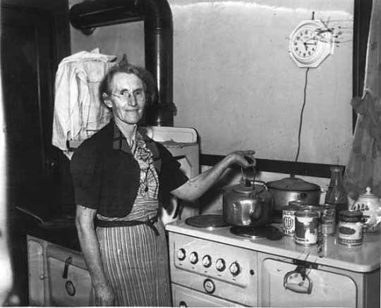 Black and white photograph of a woman standing by an electric stove, 1940. Photographed by the Minneapolis Star Journal.