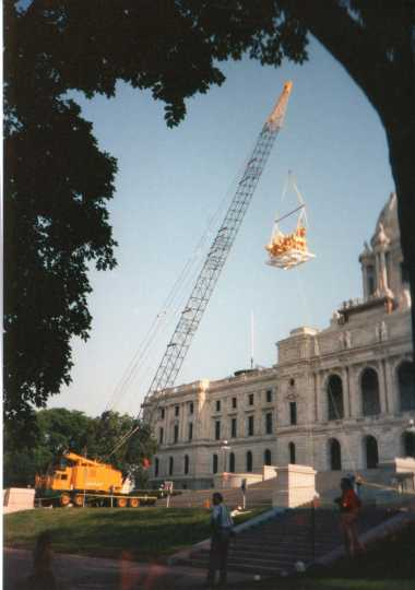Color image of a construction crane lifting the Quadriga into place over the Minnesota State Capitol's front entrance, June 21, 1995. Photographed by Linda A. Cameron