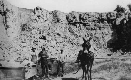 Black and white photograph of workers and a mule at a quarry in what now is Blue Mounds State Park, ca. 1880s.