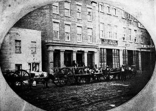 Black and white photograph of Red River Carts loading supplies at a trading house in St. Paul, 1854.