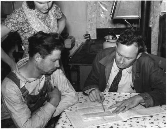 Black and white photograph of a Wilkin County farmer and his wife talk over the farm plan with the Farm Security Administration County Supervisor, ca. 1937.