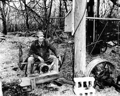 Black and white photograph of W. A. Benitt with electric pump at the windmill, 1938.