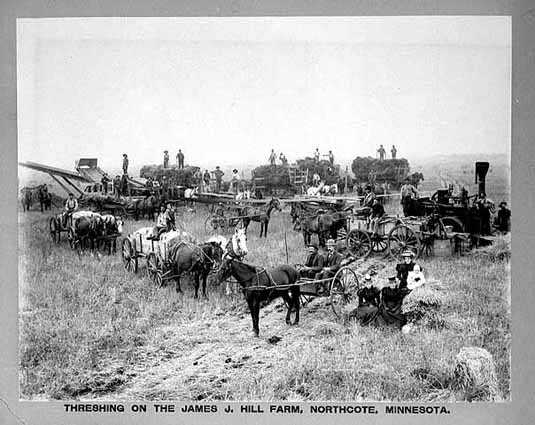 Black and white photograph of workers threshing on the James J. Hill farm, Northcote, c.1900. Photograph by A.H. Anderson.