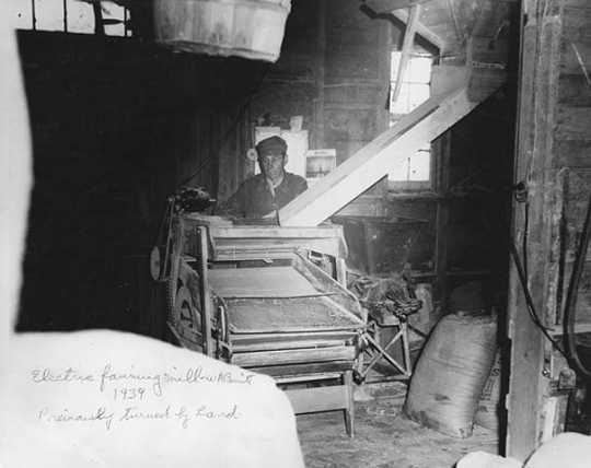 Black and white photograph of a man operating electric fanning mill, W. A. Benitt farm, Dakota County, 1939.