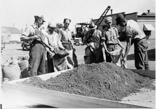 Black and white photograph of WPA crew mixing grasshopper bait for distribution to farmers, State Highway Maintenance Shops at Hopkins, 1937.