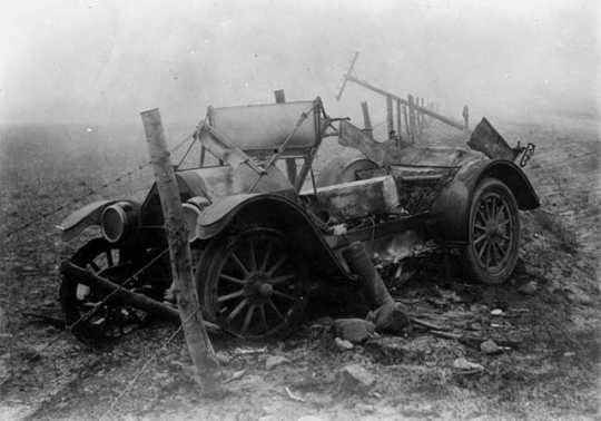 Black and white photograph of the ruins of a car after fire, Kettle River Road, 1918.