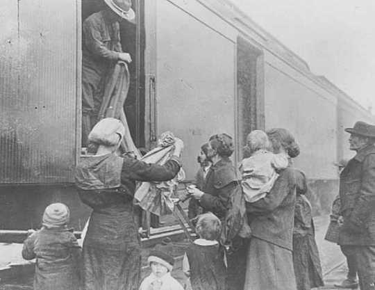 Black and white photograph of the National Guard giving out clothing to refugees, 1918.