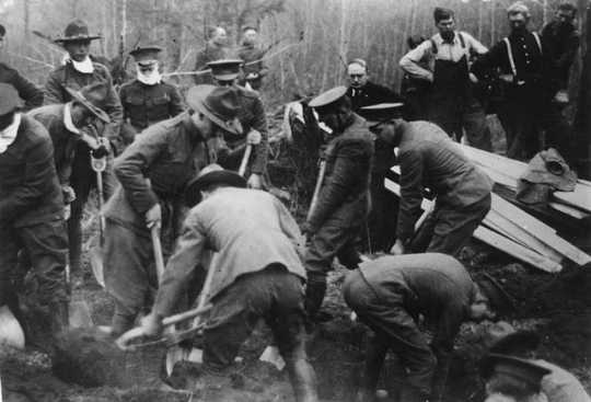 Black and white photograph of the Minnesota Home Guard digging graves after the fires, 1918. Minnesota Governor J.A.A. Burnquist looks on (hatless, at center back).