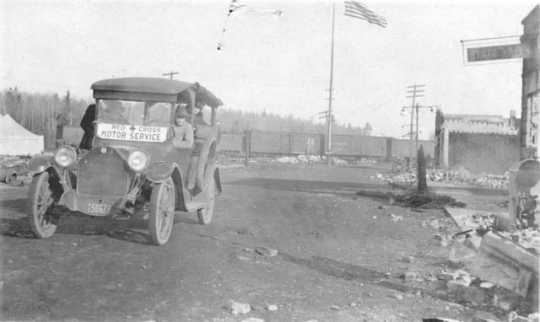 Black and white photograph of Red Cross Motor Service car providing relief efforts after the October fires of 1918.