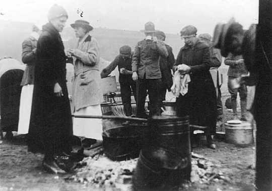 Black and white photograph of Red Cross workers serving meals to National Guard and survivors, Moose Lake forest fire, 1918.
