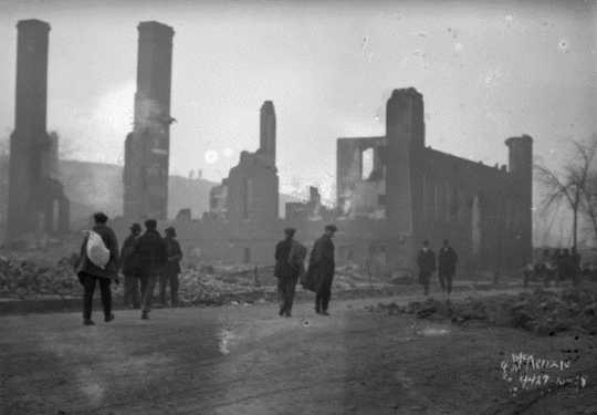 Black and white photograph of people and ruins after the fire, 1918.