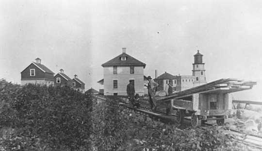 Black and white photograph of Split Rock Light Station and a tram car c.1916.